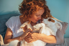 Young Woman Cuddling With Her Dog On Bed