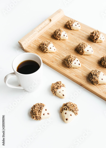 Pecan and dark chocolate covered hedgehog cookies on wooden tray with coffee