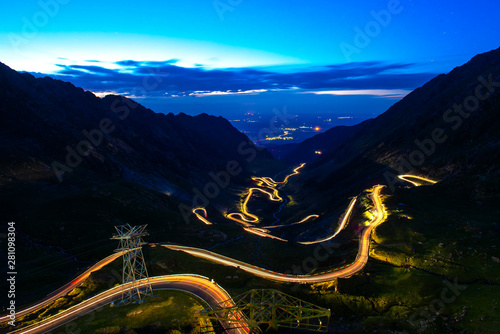 Photo Stands Black Traffic trails on Transfagarasan pass at night. Crossing Carpathian mountains in Romania, Transfagarasan is one of the most spectacular mountain roads in the world