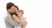 Adorable Millennial Family Embracing At Home, Empty Space