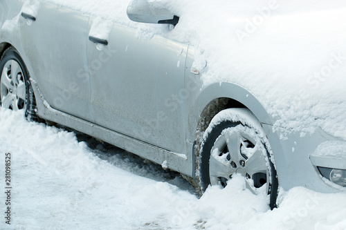 Parking car after snowfall. Automobile covered with snow. Winter concept.