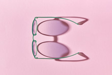 Stylish Women's Sunglasses In Green Frame With Shadows On A Pink Paper Background.