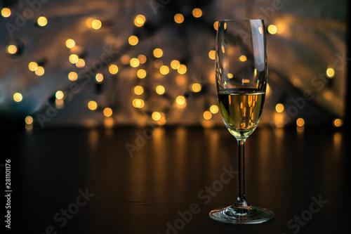 Obraz Copa de champaña con fondo negro y bokeh dorado y azul. - fototapety do salonu