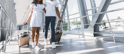 Obraz African couple walking with luggage in airport - fototapety do salonu