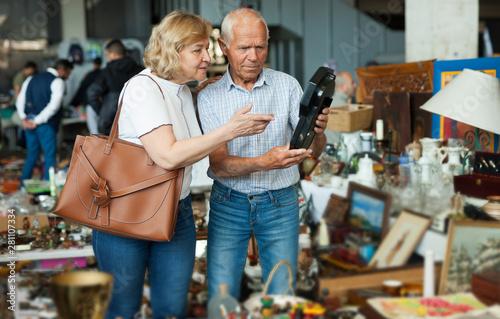 Valokuva  Elderly couple in flea market chooses antique items