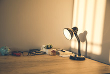 Working Table With Lamp On Wall Background In Evening