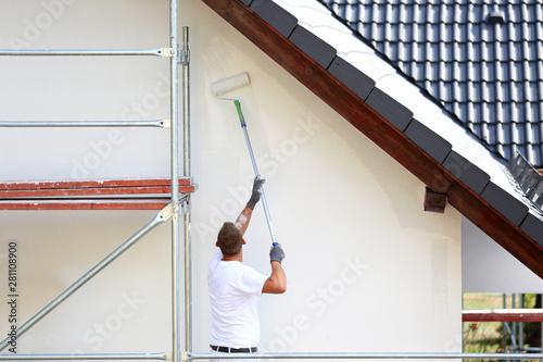 Malowanie wałkiem elewacji budynku na rusztowaniu. - fototapety na wymiar