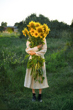 Girl Holding A Large Bouquet Of Sunflowers