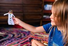 Little Girl Holds Up Paper Doll She Made