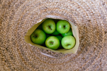 Paper Bag Of Green Apples On Jute Rug, From Above