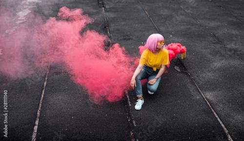 Fotografiet  Trendy teen hipster sitting near smoke bomb