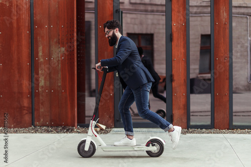 Bearded businessman riding to work on electric scooter