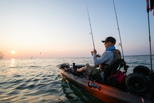 Young Man Kayak Fishing At Sunrise In Canada