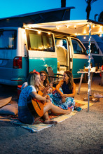 Group Of Happy People Playing The Guitar Together And Chatting Near Camper Van, After Dinner. Holiday And Friendship Concept.
