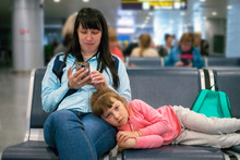 Mom And Sad Child Are Waiting For Their Plane At The Airport. The Little Girl Is Lying On Her Mother's Feet In The Waiting Room. Passengers Are Waiting For Their Transport In The Station