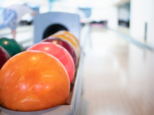 Closeup Of Vivid Orange Bowling Ball. Selective Focus On Foreground With Blurred Track Lane On Background