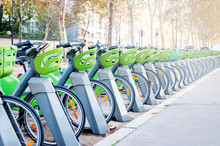 Parking With A Large Number Of Electric Bikes For Renting And Driving Around The City. Autumn Sunny Day. Close-up