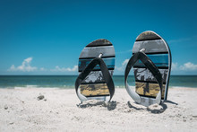 Pair Of Flip Flops In White Beach Sand With Blue Ocean At Background. Perfect Day At Vocations