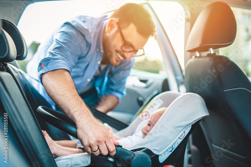 Fotomural  Young father putting his baby boy on a safety child car seat.