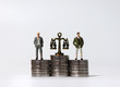 canvas print picture - Miniature men standing on a pile of coins of the same height. Pile of coins and a miniature scale.