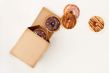 Paper Box With Assortment Of Falling Donuts. Top View. Space For Text.