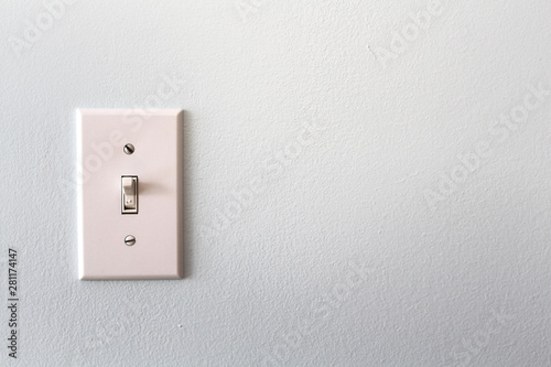Fotografía  A white light switch on a grey wall
