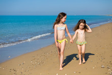 Little Girls In Swimsuits On The Beach Walking, Holding Hands. Children On Vacation. Family Vacation. Happy Sisters