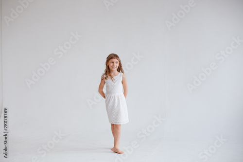 Fotografija girl in white dress dancing on white background