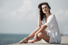 Beautiful Girl In White Dress On Seacoast. Girl In Summer White Dress Sitting On The Shore.Beautiful Slender Thin Girl Sitting  By The Sea, Enjoying The Breeze. Young Woman With Beautiful Long Tanned
