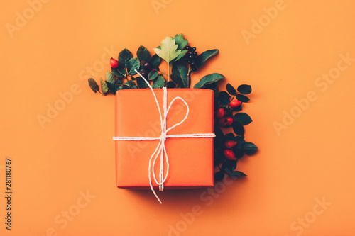 Canvas Prints Countryside Creative birthday present. Top view of handmade paper gift box with rose hip decor on orange background. Copy space.