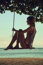Young Woman Swinging On A Sandy Tropical Beach.