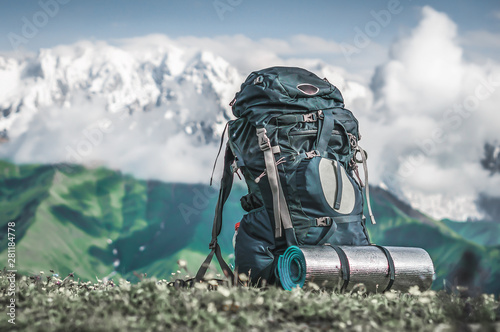 Tourist backpack and sleeping pad on a background of mountains Canvas Print
