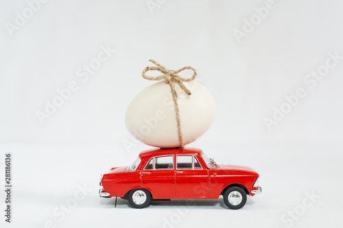 Red toy car with chicken egg on the roof Wallpaper Mural