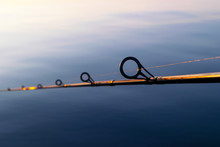 Fishing Rod Spinning Ring With The Line Close-up. Fishing Rod Over The Crystal Still Water. Fishing Rod Rings. Fishing Tackle. Fishing Spinning Reel. Soft Lighting