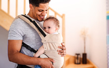 A Father With Small Toddler Son In Carrier Indoors At Home.