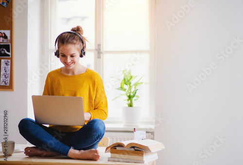 A young female student sitting at the table, using headphones when studying. - 281202960