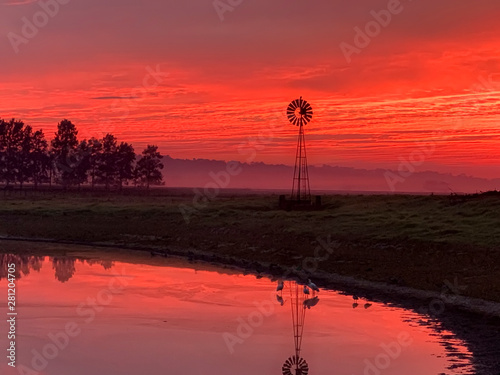 Poster de jardin Rouge Light morning fog, windmill, pond with red sunrise sky in rural countryside