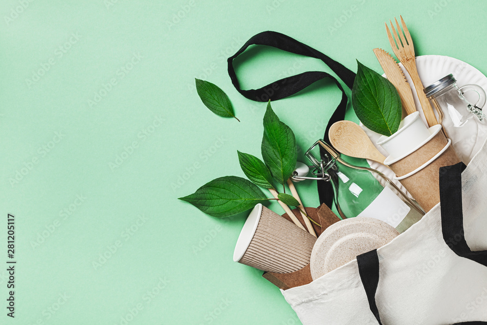Fototapeta Plastic free set with cotton bag, glass jar, green leaves and recycled tableware top view. Zero waste, eco friendly concept. Flat lay.