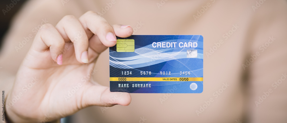 Fototapeta Young female holding credit card, Online shopping or paying concept.