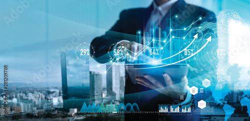 Fototapeta Digital marketing. Business strategy. Businessman using tablet analyzing sales data and economic growth graph chart on hologram screen. Business strategy and digital data. obraz