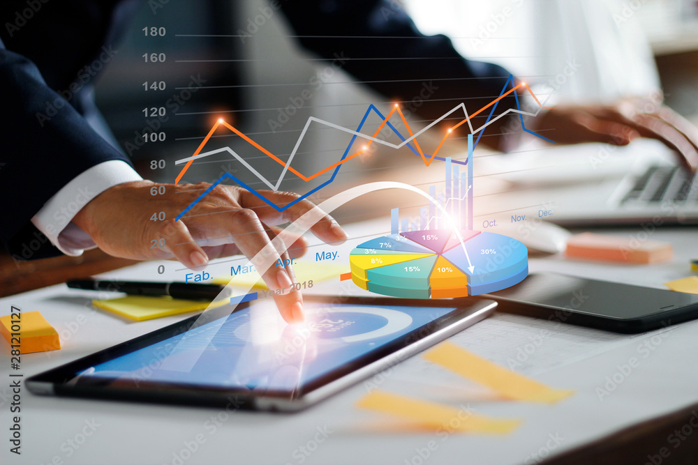 Fototapeta Businessman using tablet and laptop analyzing sales data and economic growth graph chart. Business strategy. Digital marketing. Business innovation technology concept