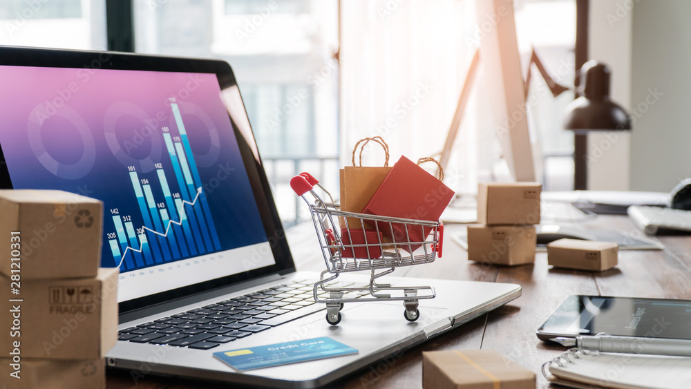 Fototapeta Shopping bags incart and credit card on laptop with paper boxes on table and sales data economic growth graph on screen, buying and selling services online on network, e-commerce concept