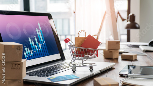 Fototapeta Shopping bags incart and credit card on laptop with paper boxes on table and sales data economic growth graph on screen, buying and selling services online on network, e-commerce concept obraz