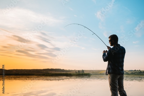 Fotografie, Obraz  Fisher man fishing with spinning rod on a river bank at misty foggy sunrise