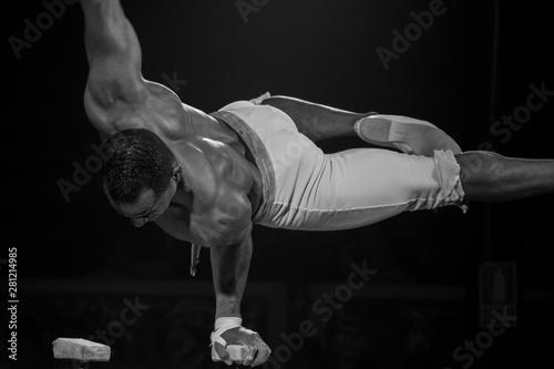 musculoso gimnasta haciendo entrenamientos, fondo negro Canvas Print