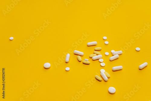Tablets, pills and other medicine scattered on the orange background Fototapeta
