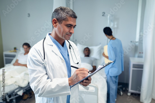 Fotografiet  Male doctor writing on clipboard in the ward at hospital