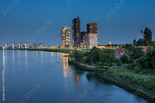 Montage in der Fensternische Rotterdam luminated tall apartment buildings at the riverside after sunset. Spijkenisse skyline at the Oude Maas river. With small house surrounded by green and wave breakers rocks at the shoreline