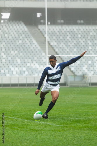 African American male rugby player kicking rugby ball in stadium