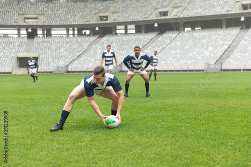 Diverse male rugby players playing rugby match in stadium